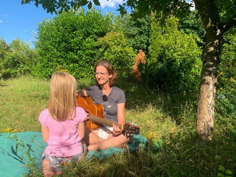 Annette spielt Gitarre auf einer Wiese